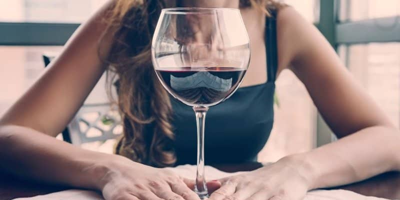 woman with big glass of wine waiting for effects of alcohol