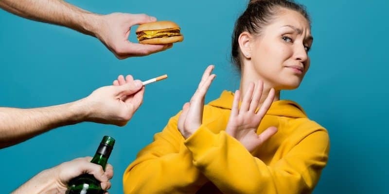 woman resisting being offered several items of bad habits