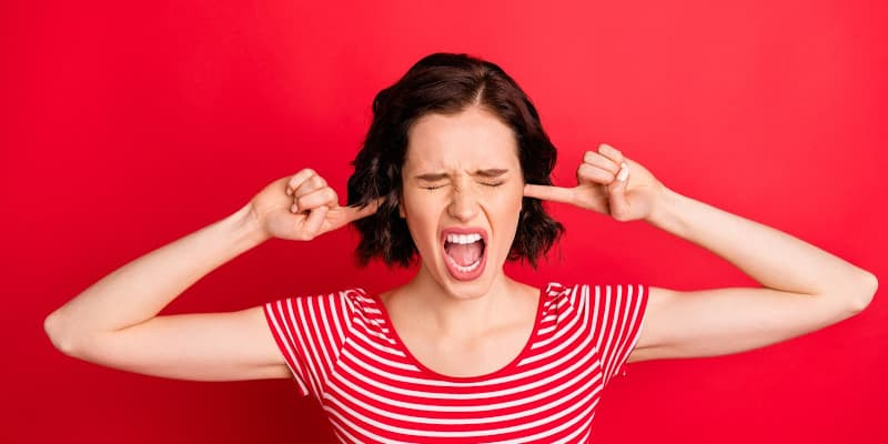 Angry woman plugging her ears