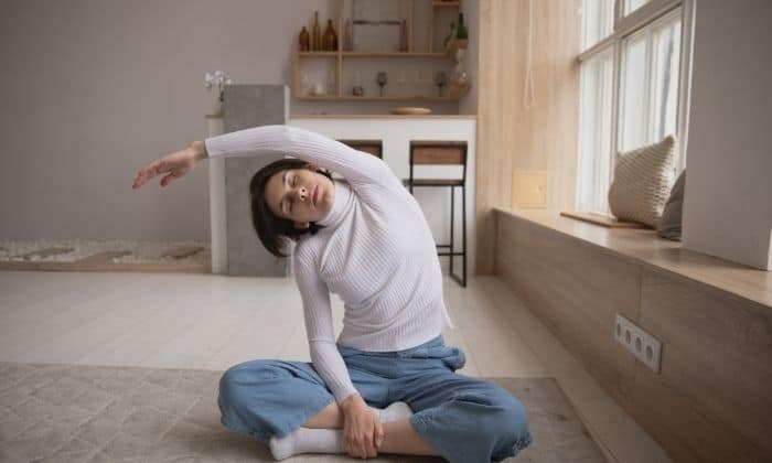 woman stretching on floor to help manage her anxiety