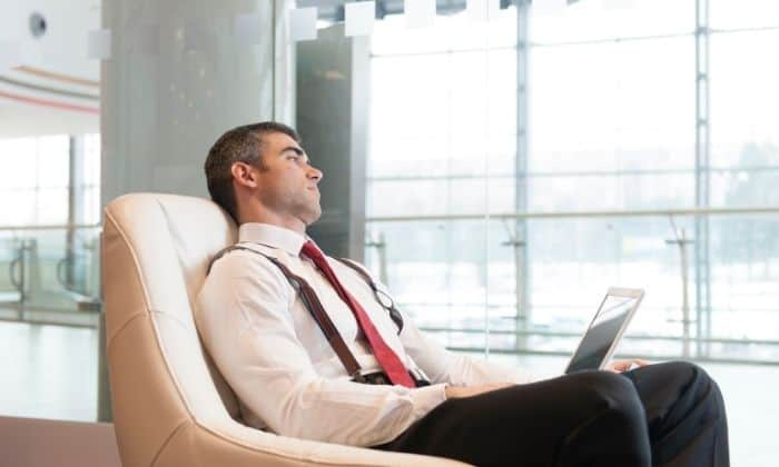 man with anxiety sitting on chair staring out of window