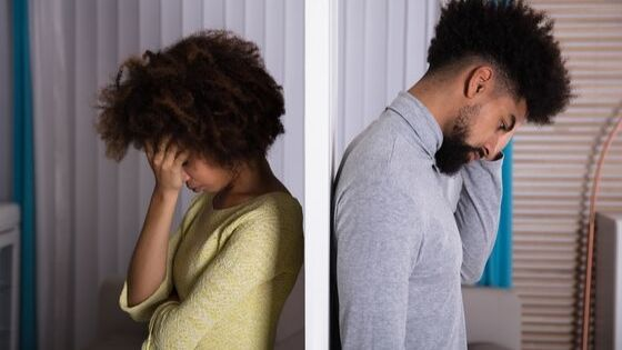 couple facing back to back struggling with addiction in their marriage