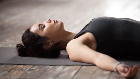 stressed woman lays down in shavasana
