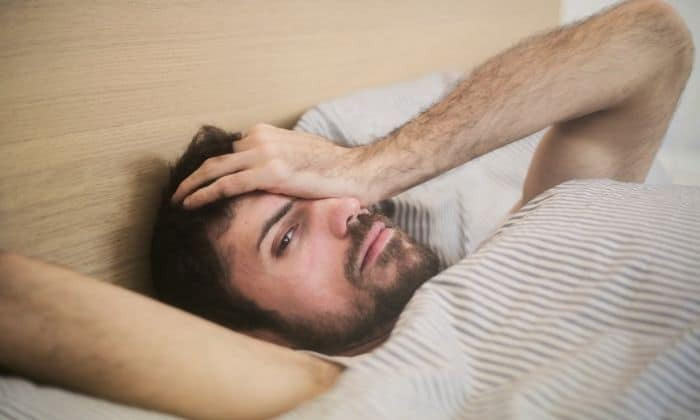 man suffering from hangxiety in bed