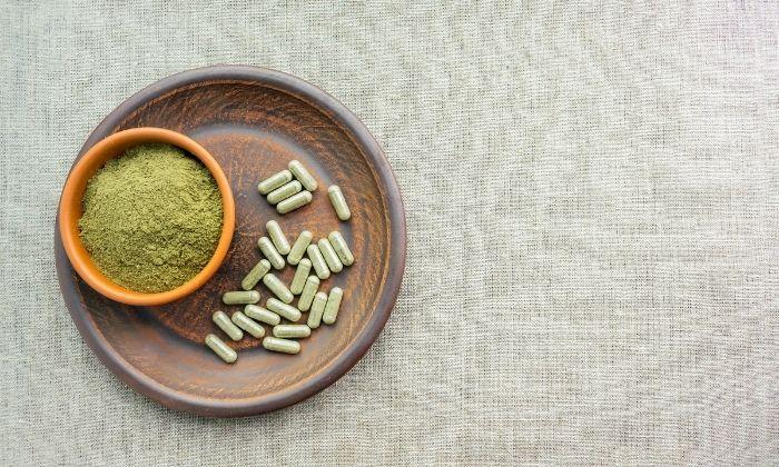 kratom vs kava kratom powder and pills on wooden plate