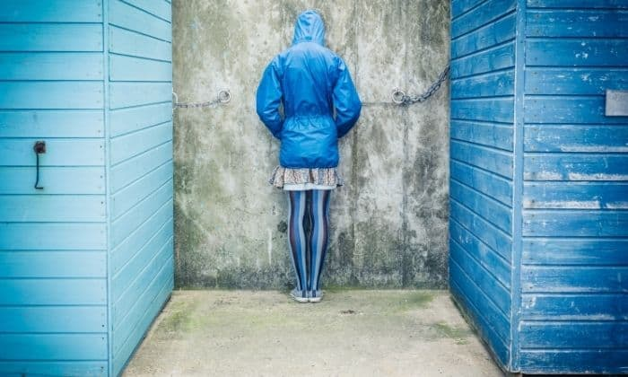 Woman feeling shame facing a wall