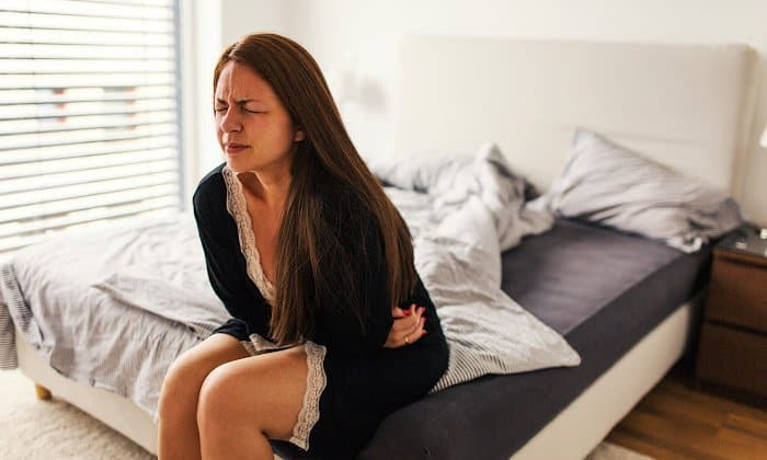 woman clutching stomach after having diarrhea from alcohol